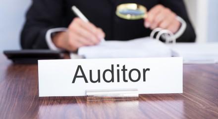 Bordje auditor met achtergrond mannenhanden met pen en loep