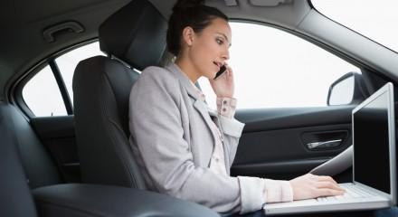 Vrouw in auto belt met mobiel en heeft laptop op schoot