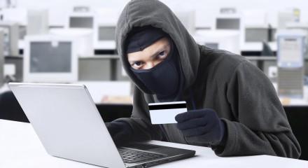 Man met bivakmuts achter laptop met ID kaart
