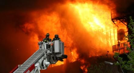 Brandweermannen op uitschuifladder bij huis dat in de brand staat